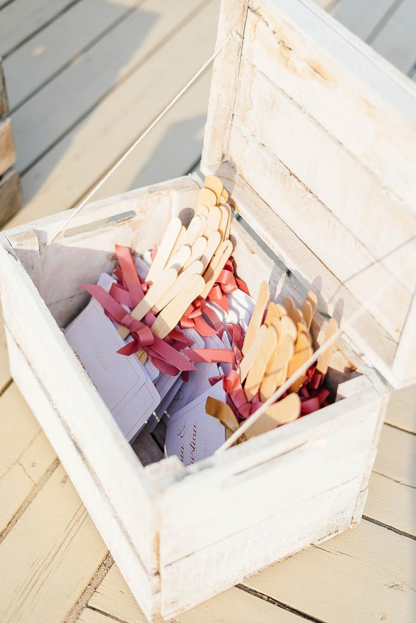 fan wedding ceremony programs with wooden handles in crate