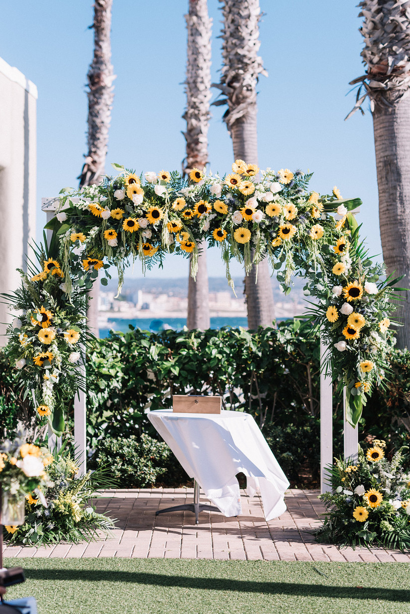 sunflower wedding ceremony arch with yellow gerbera daisies, white roses and greenery