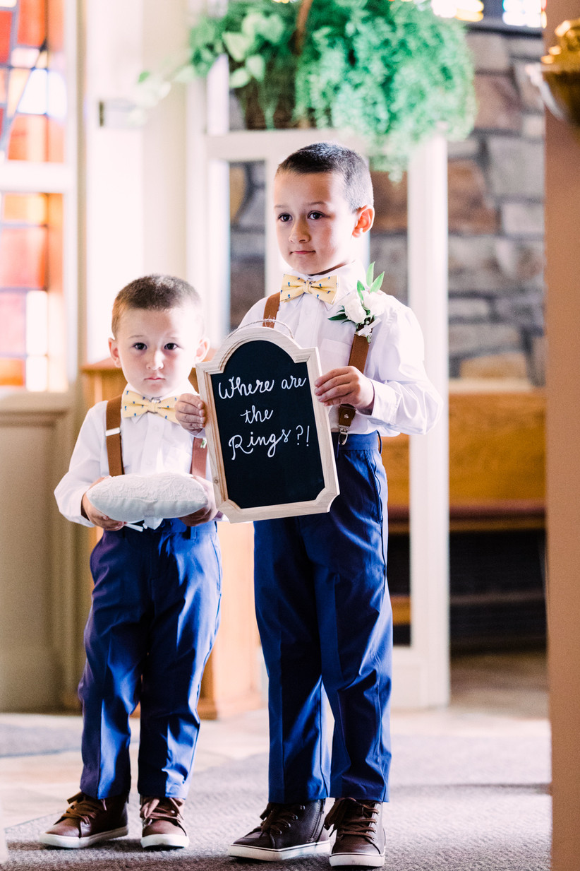 """two ring bearers dressed in suspenders with one carrying a chalkboard sign that says """"where are the rings?"""""""