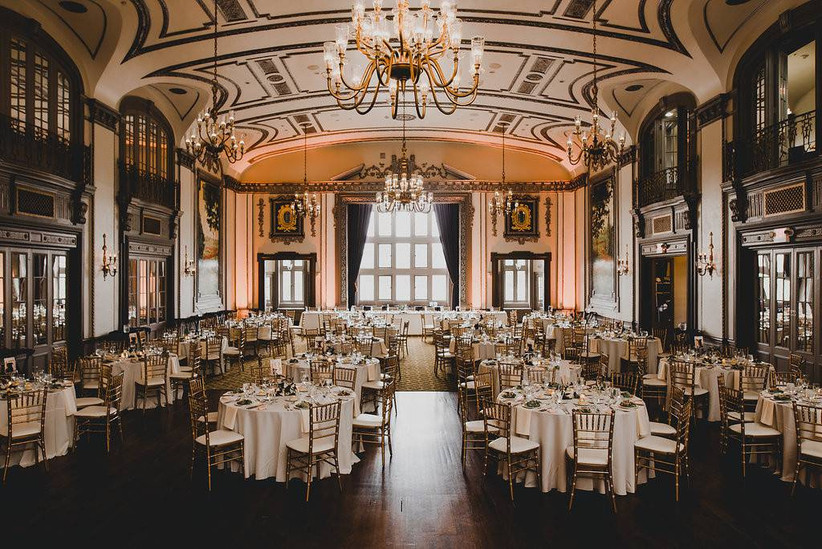 ornate ballroom with chandeliers set up for a wedding with gold chairs and ivory table linens