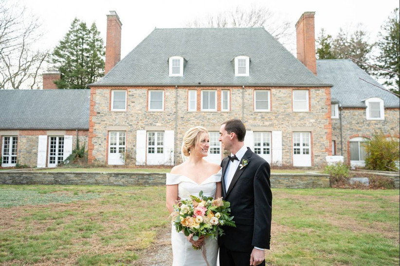 bride and groom stand in front of brick mansion and smile at each other at rhode island wedding venue