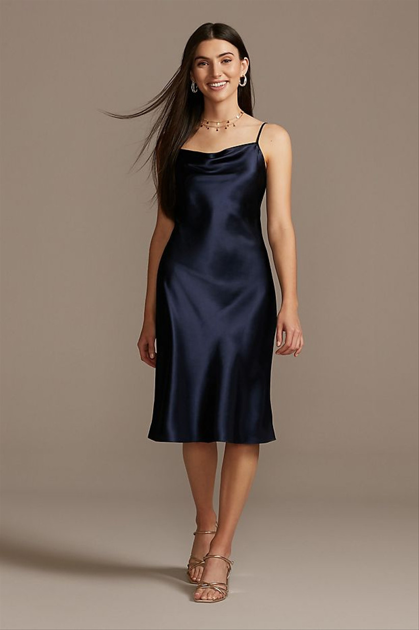 Model smiles and looks at camera while wearing mid-length navy blue bridesmaid dress with cowl neckline
