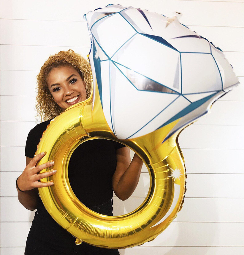 Woman holding giant gold foil diamond engagement ring balloon