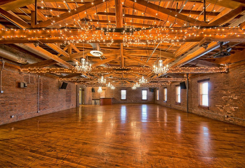 industrial event space with string lights, wood beam ceilings, chandeliers, and wood flooring