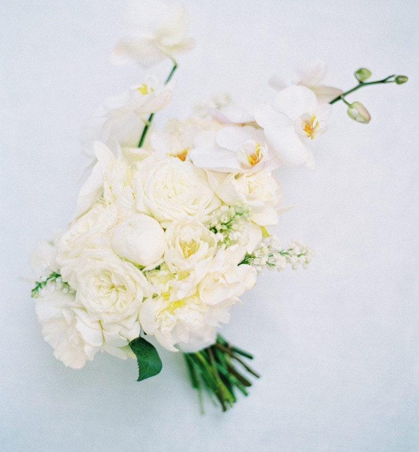 all-white beach wedding bouquet with garden roses peonies and asymmetrical phalaenopsis orchid stems