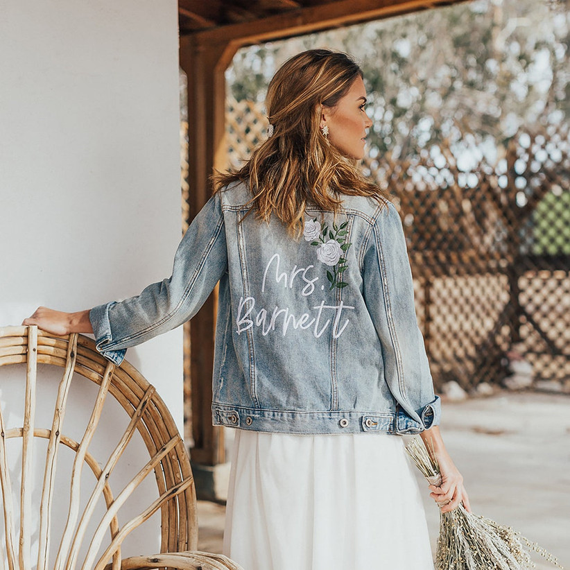 denim bridal jacket embroidered with white flowers and bride's last name in white calligraphy font