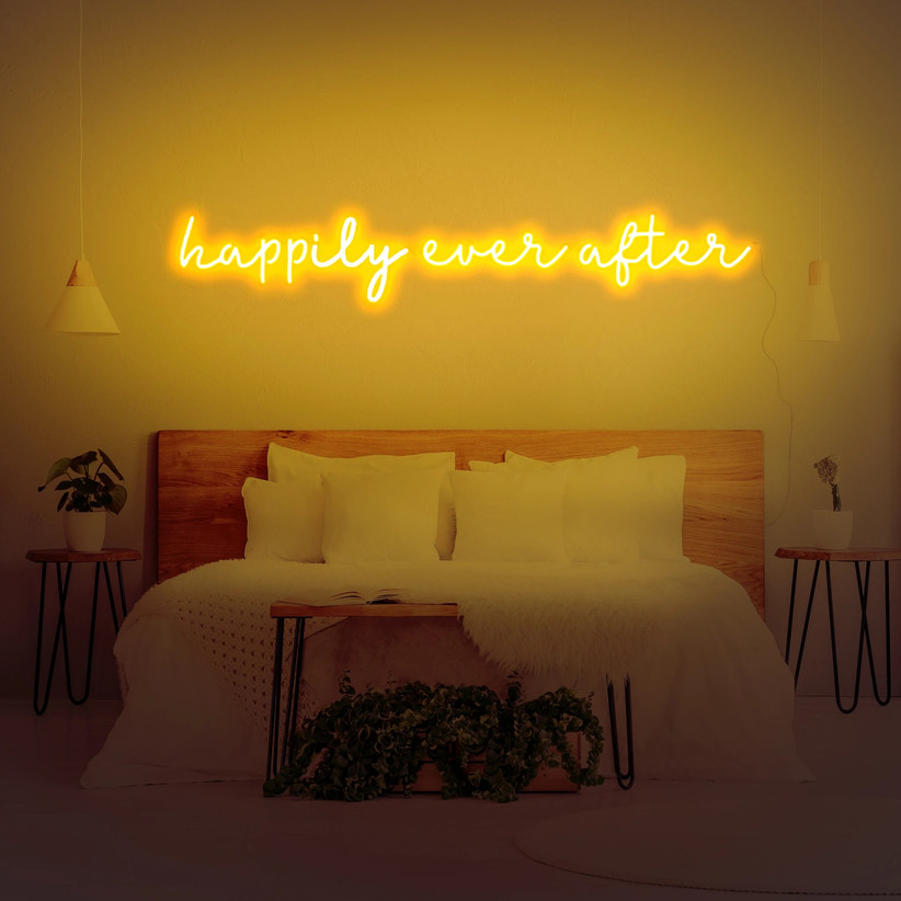 Happily Ever After yellow neon sign above a bed