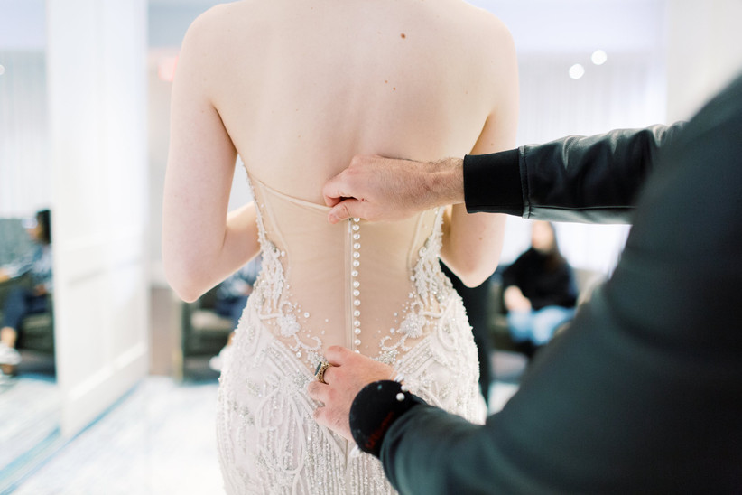 bride trying on wedding dress with buttons down back