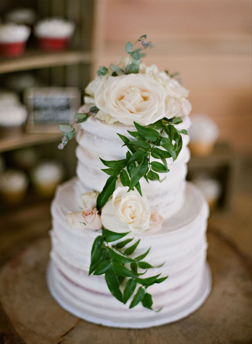 buttercream wedding cake decorated with roses and greenery