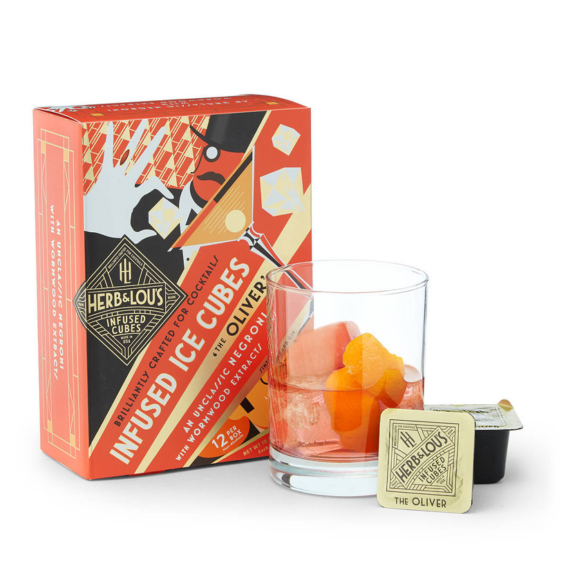 Box of cocktail-infused ice cubes next to glass with a cocktail