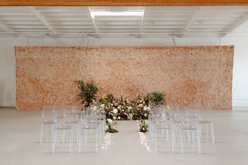indoor ceremony setup with wedding flower trends colorful abstract floral wall surrounded by clear lucite chairs