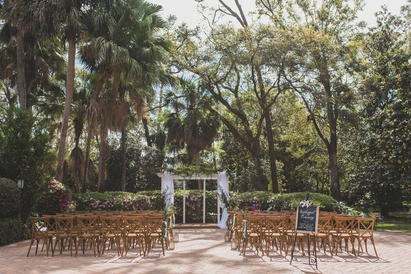outdoor wedding ceremony brick courtyard surrounded by trees and flower bushes