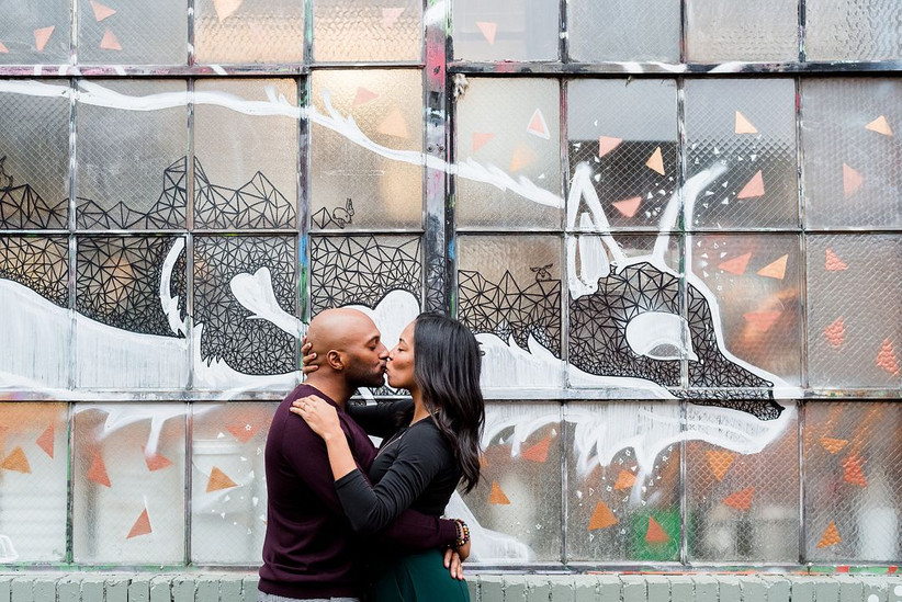 black couple kisses while standing in front of mural painted onto a large window