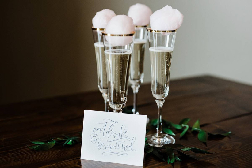 champagne flutes topped with balls of pink cotton candy
