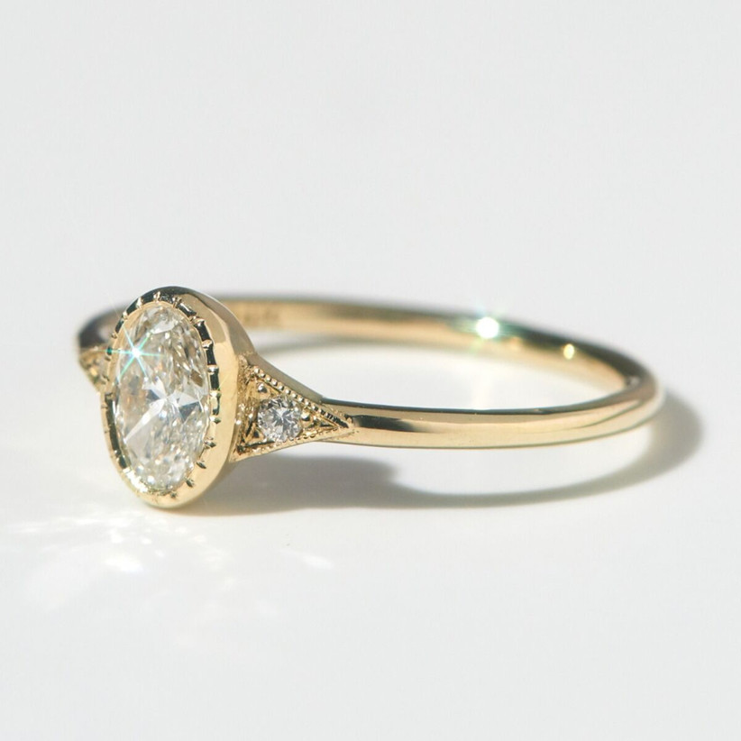 Minimalist three-stone diamond engagement ring with yellow gold band
