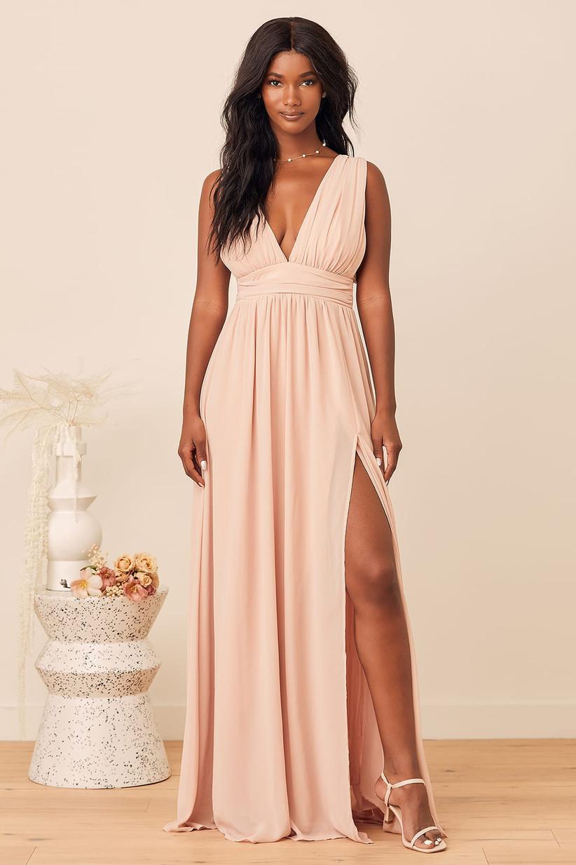 Model wearing deep V-neck pastel pink bridesmaid dress with leg slit