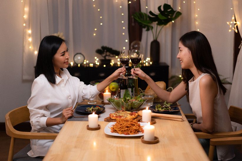 LGBTQ+ couple toasting wine glasses over a romantic dinner