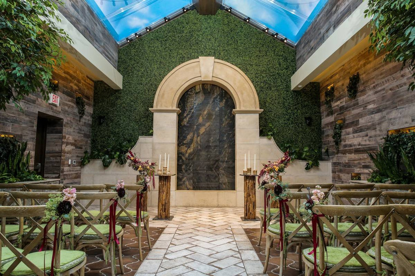 las vegas wedding chapel with skylights and garden-inspired decor featuring moss wall behind the altar and brick flooring