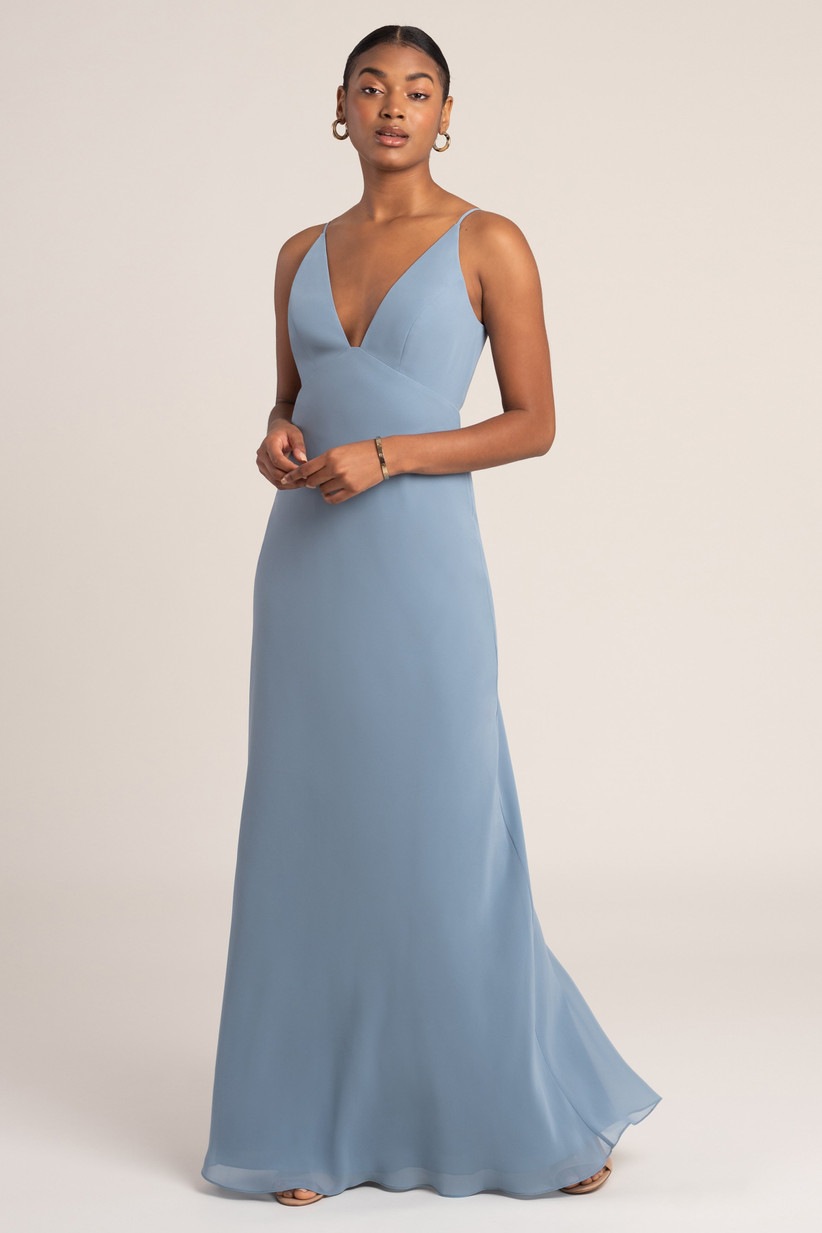 Black model looks at the camera wearing a light blue bridesmaid dress trend with empire waist and spaghetti straps