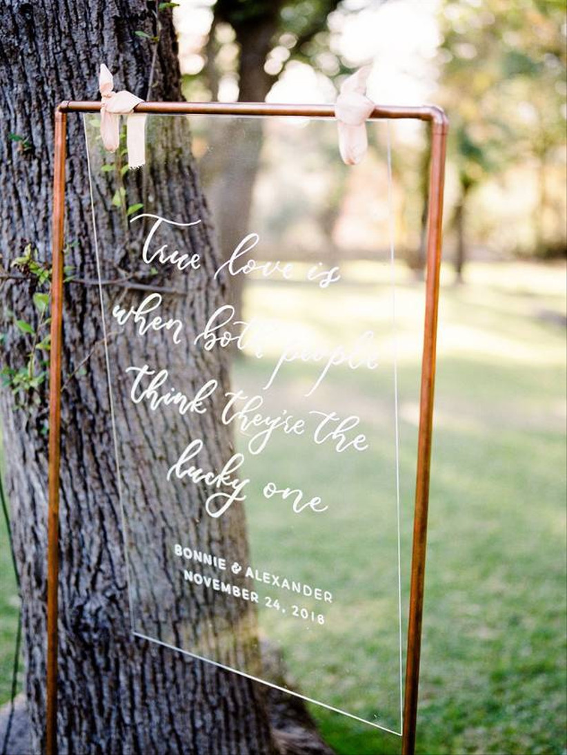 clear acrylic wedding sign displaying white calligraphy hanging from copper metal frame