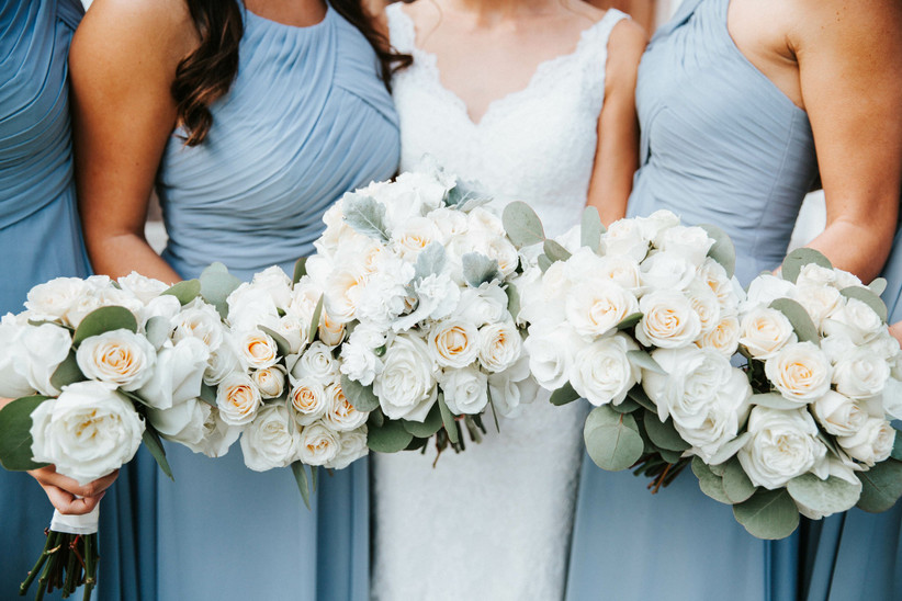 bride and bridesmaids hold their white rose beach wedding bouquets next to each other
