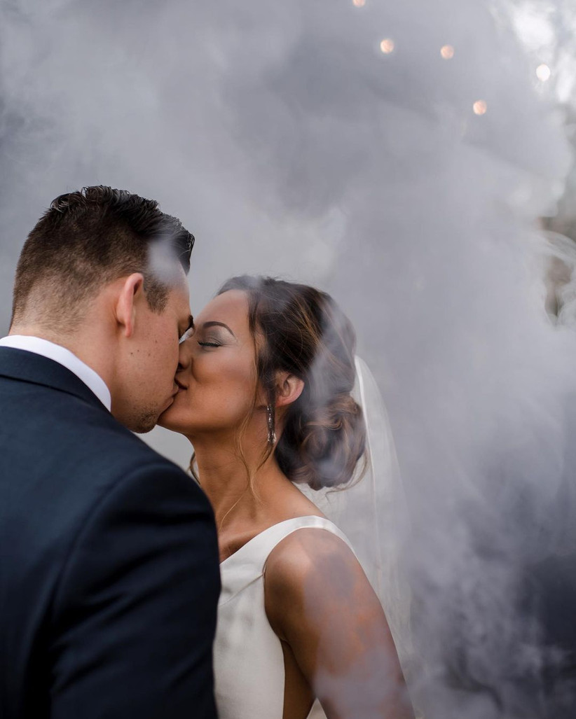 bride and groom kiss while white smoke surrounds them celestial wedding theme photo effect