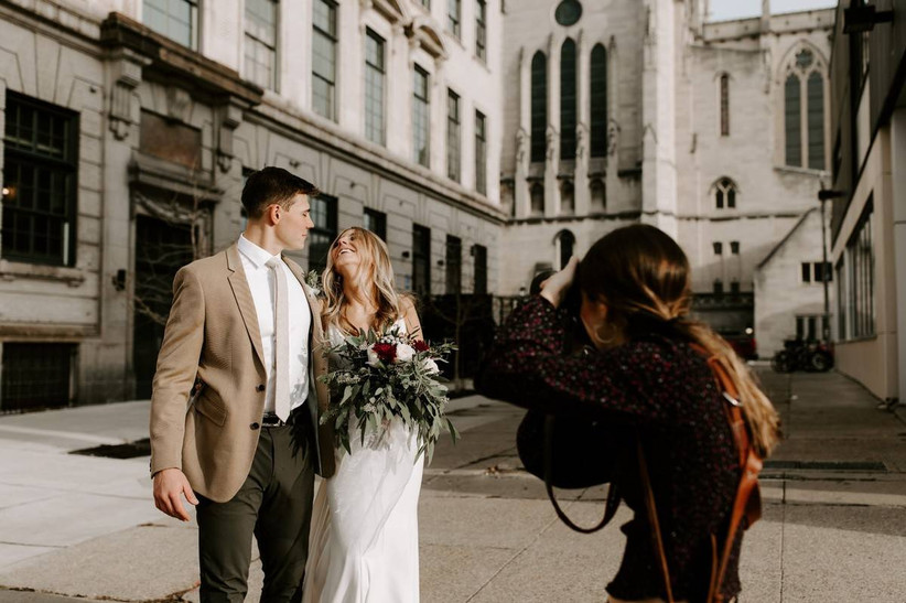 wedding photographer taking a photo of happy couple