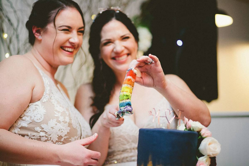 same-sex wedding two brides smile for the camera while holding a piece of rainbow layer wedding cake