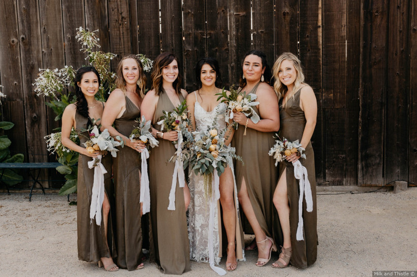 Bridesmaids wearing green dresses with brown undertones in photo with bride