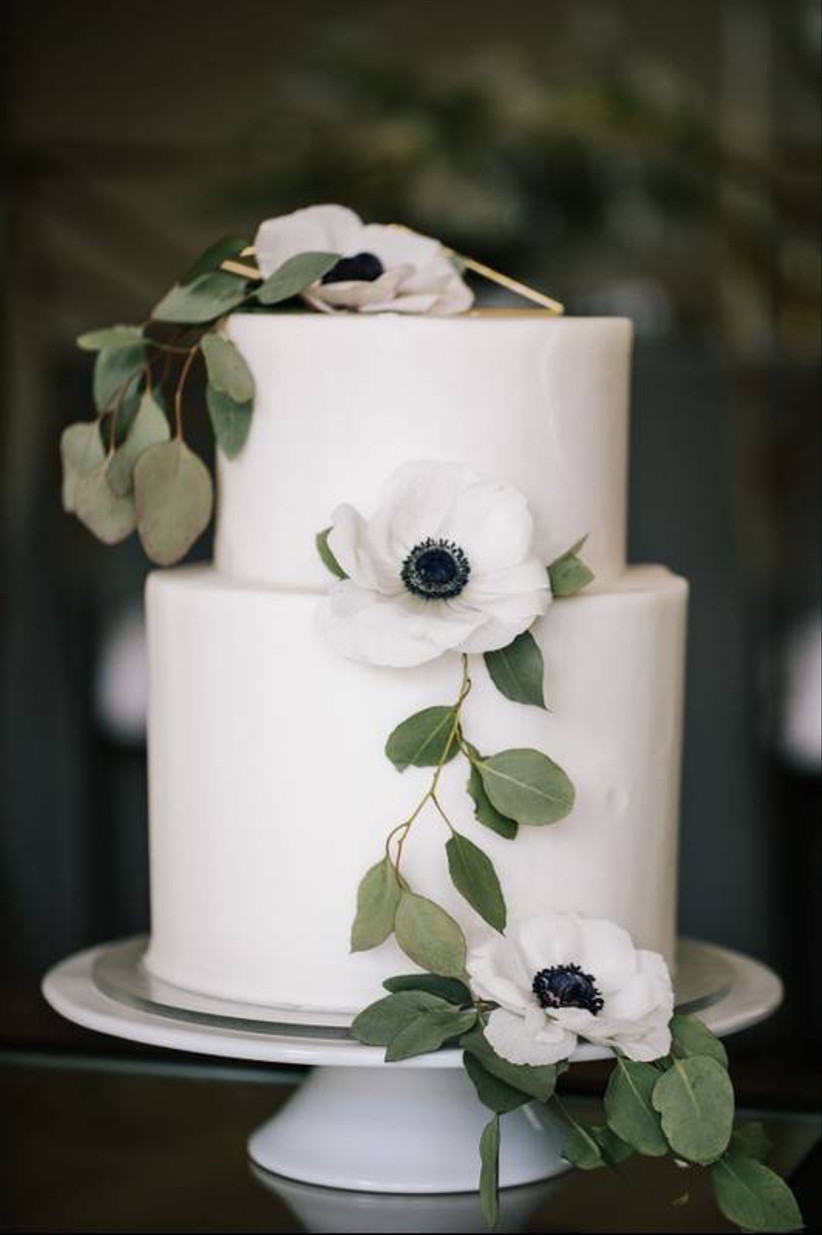 simple wedding cake decorated with white flowers and greenery