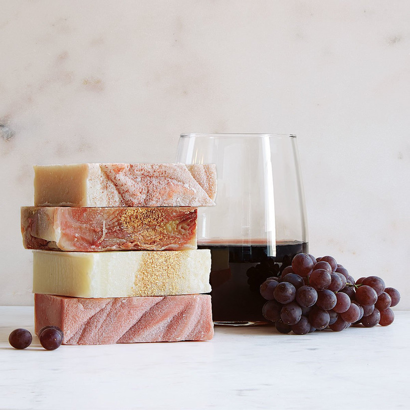 Wine-inspired soaps stacked next to glass of wine