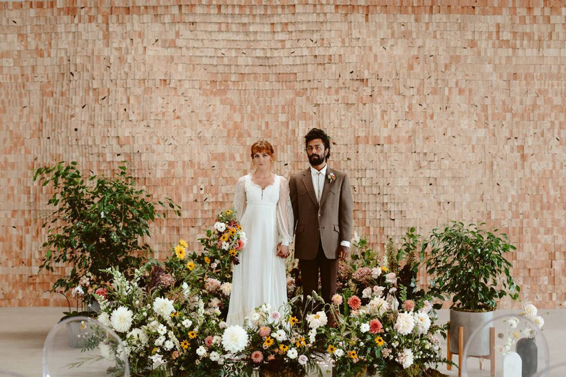 bride and groom stand in the middle of a floral circle at their indoor ceremony altar with overgrown garden-inspired flowers in pink, white, yellow