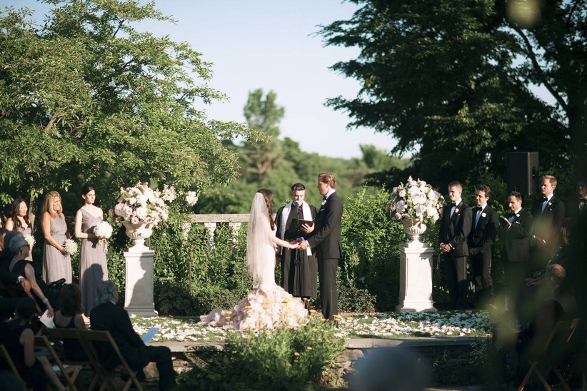 bride and groom hold hands at outdoor wedding ceremony english-garden style venue