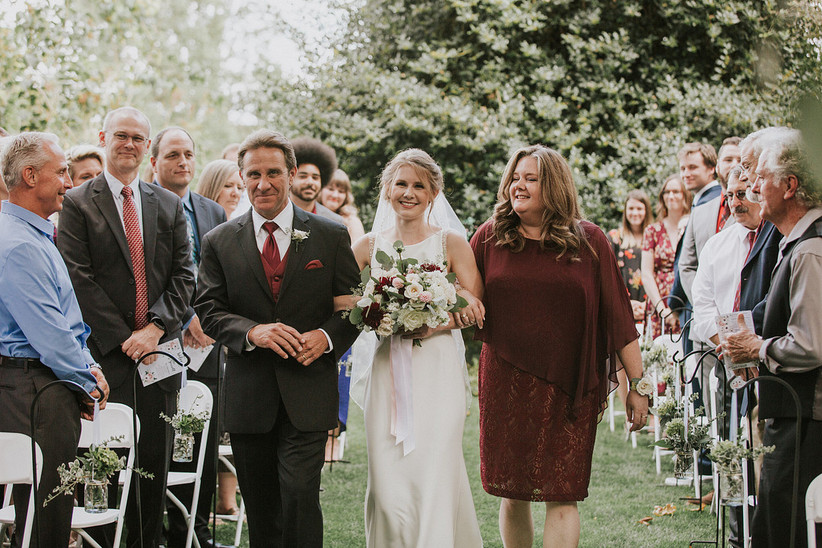 Bride's mom and dad walking her down the aisle with guests watching and wearing fall wedding attire