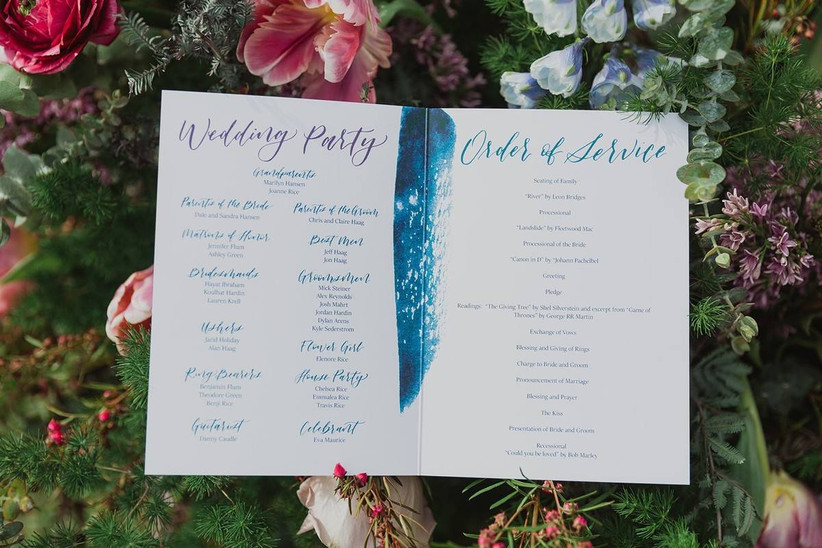 watercolor wedding ceremony program booklet is displayed on a bed of flowers and greenery