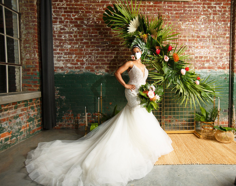 Black bride stands in front of tropical floral ceremony backdrop against an indoor brick wall. She is wearing a wedding dress with a long train and a protective face mask decorated with a flower