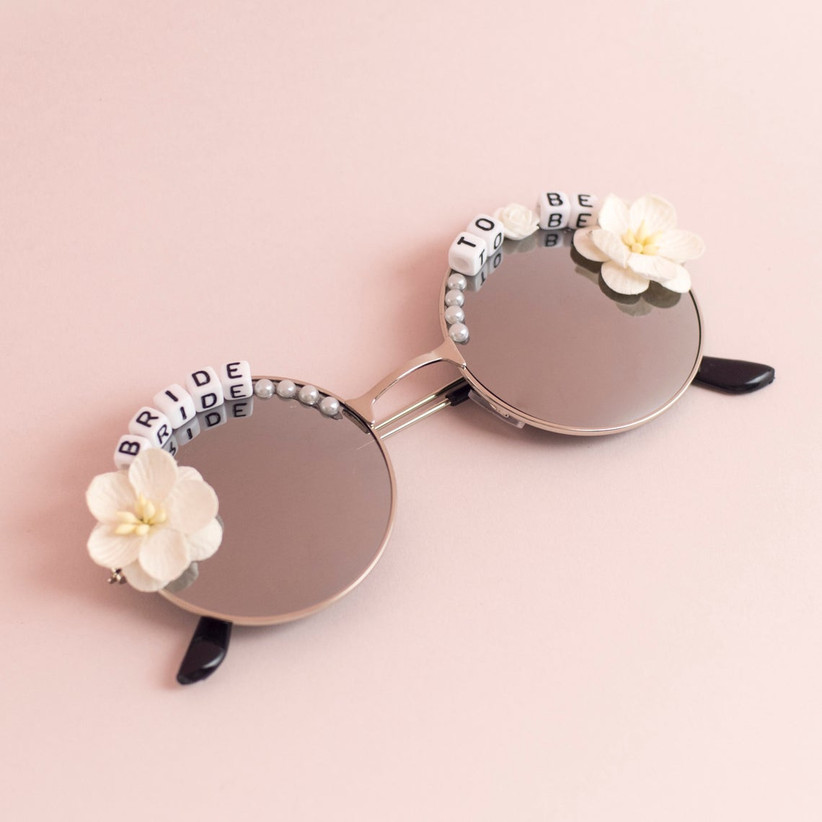 round sunglasses with fabric flowers and letter beads that spell bride-to-be