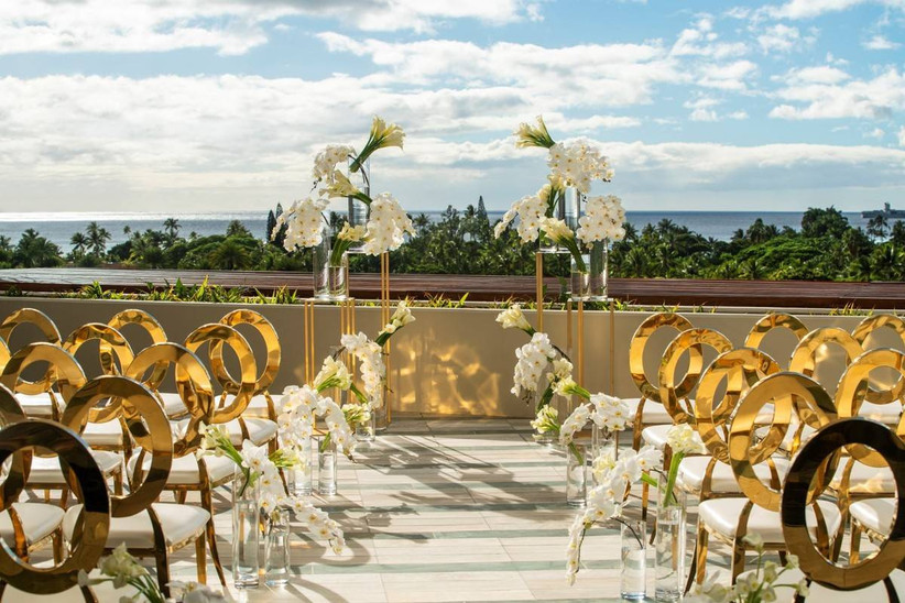 outdoor wedding ceremony with glamorous gold chairs and white calla lily flower arrangements on rooftop overlooking the ocean