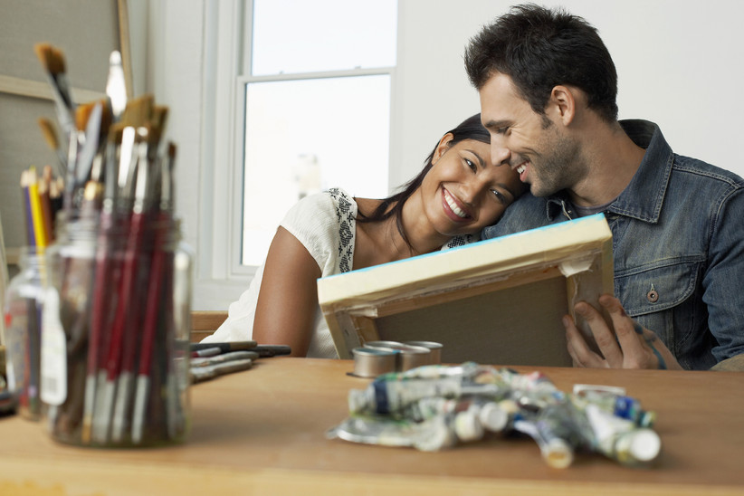 Couple smiling and holding a painting with art materials on the table