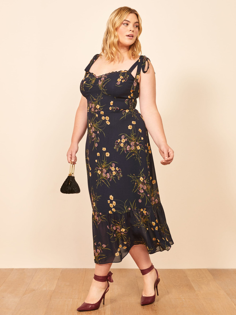 Plus size model wearing black midi with tie-at-the-shoulder straps, pretty wildflower print, and sweetheart neckline