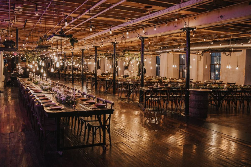 indoor wedding reception in industrial space with exposed wood beam ceilings and columns