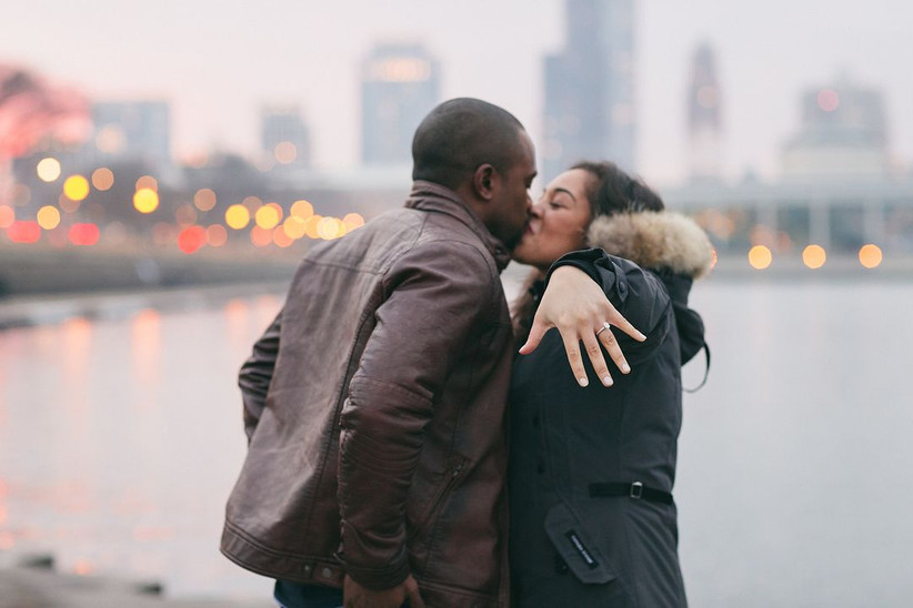 newly-engaged black couple kisses as bride shows her engagement ring off for the camera
