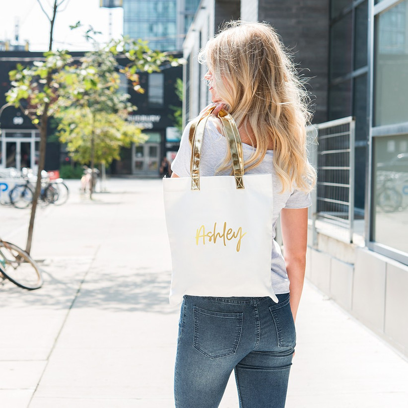 Model outdoors turned away from camera with white and gold tote bag over her shoulder personalized with her name