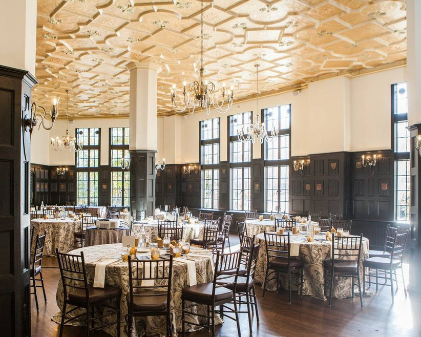 castle-style boston wedding venue ballroom with dark wood panel walls, floor to ceiling windows and chandeliers