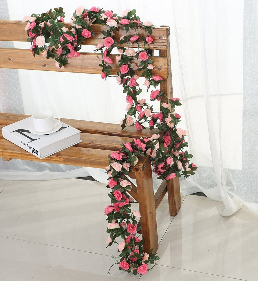Artificial greenery and pink floral garland draped over a wooden bench