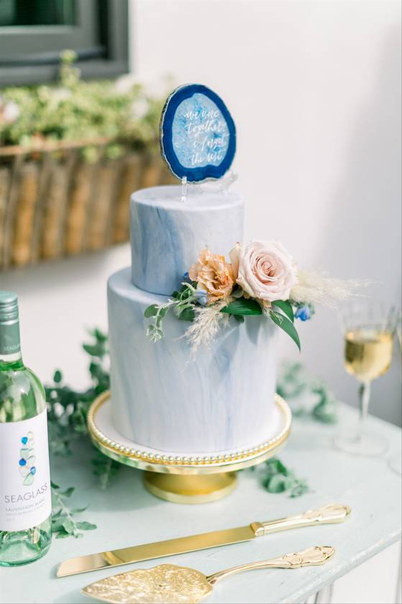 blue wedding cake decorated with marbled pattern and fresh flowers