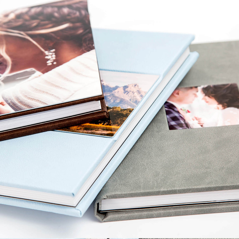 Close-up of three photo books in different colors and styles