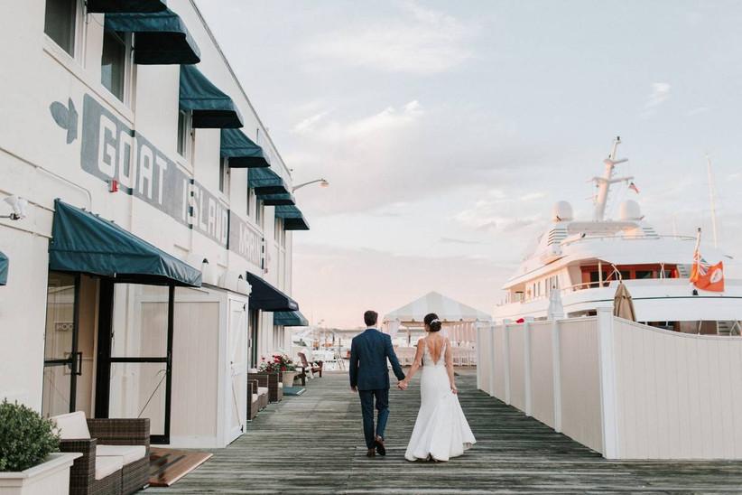 groom and bride walking down dock