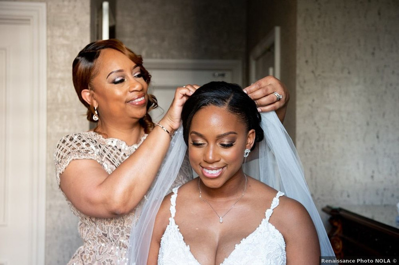 mother of the bride places veil in bride's hair
