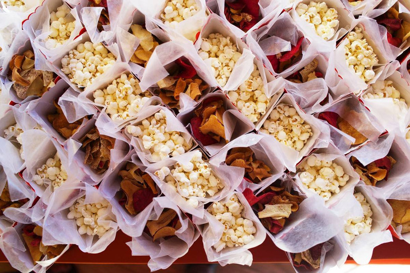 individual paper cartons of popcorn and tortilla chips are lined in rows on a table